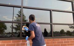 An ABM Maintenance Worker sanitizes a lunchroom window.