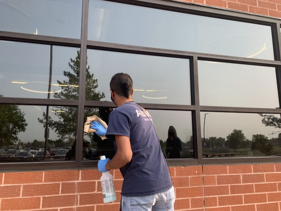 An ABM Maintenance Worker sanitizes a lunchroom window.